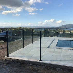 semi-frameless glass pool fence enclosing a pool overlooking a valley
