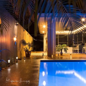 pool area with frameless glass pool fence at night